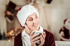 Ικανοποιημένη ρομαντική γυναίκα που κοιτάζει κατά μέρος και που κρατά ένα φλυτζάνι στοκ φωτογραφία με δικαίωμα ελεύθερης χρήσης