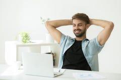 Ικανοποιημένη χαλάρωση εργαζομένων στην καρέκλα στο γραφείο κατά τη διάρκεια του σπασίματος εργασίας στοκ εικόνες