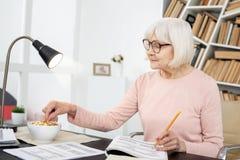 Ικανοποιημένη ώριμη γυναίκα που τρώει κατά τη διάρκεια της μελέτης Στοκ φωτογραφία με δικαίωμα ελεύθερης χρήσης