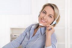 Ικανοποιημένη ώριμη επιχειρηματίας με το ακουστικό στο γραφείο. Στοκ Εικόνα