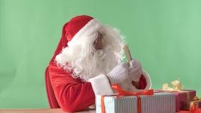 Ικανοποιημένος Άγιος Βασίλης μετρά τα δολάρια, τα χρήματα, και την παρουσίαση όπως το σημάδι, chromakey στο υπόβαθρο απόθεμα βίντεο
