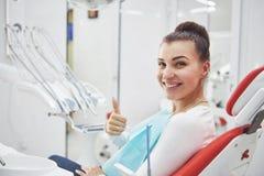 Ικανοποιημένος ασθενής που παρουσιάζει τέλειο χαμόγελό της μετά από τη θεραπεία σε μια κλινική οδοντιάτρων στοκ εικόνες