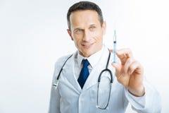 Ικανοποιημένος γιατρός που ελέγχει τη σύριγγα πριν από την έγχυση Στοκ φωτογραφία με δικαίωμα ελεύθερης χρήσης