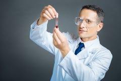 Ικανοποιημένος επαγγελματίας που εξετάζει το δείγμα αίματος Στοκ φωτογραφίες με δικαίωμα ελεύθερης χρήσης