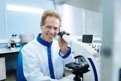 Ικανοποιημένος ερευνητής με ένα μικροσκόπιο στο εργαστήριο Στοκ Φωτογραφία