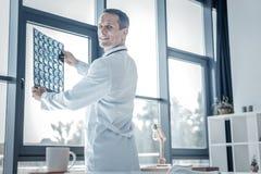 Ικανοποιημένος ευχάριστος γιατρός που κρατά την των ακτίνων X ανίχνευση και το χαμόγελο Στοκ Εικόνες