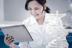 Ικανοποιημένος θηλυκός επιστήμονας που χαμογελά εξετάζοντας τον υπολογιστή ταμπλετών Στοκ Φωτογραφίες