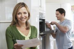 Ικανοποιημένος θηλυκός πελάτης με την επισκευή Μπιλ φούρνων Στοκ Εικόνα