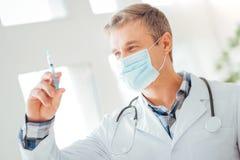 Ικανοποιημένος καταρτισμένος γιατρός που στέκεται και που εξετάζει τη σύριγγα Στοκ εικόνες με δικαίωμα ελεύθερης χρήσης