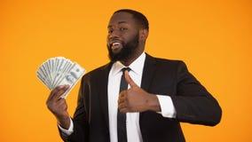 Ικανοποιημένος μαύρος επιχειρηματίας που παρουσιάζει τα μετρητά δολαρίων και αντίχειρας-επάνω χειρονομία, εισόδημα απόθεμα βίντεο