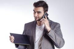 Ικανοποιημένος νέος επιχειρηματίας που μιλά στο τηλέφωνο κυττάρων Στοκ Εικόνα