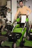 Ικανοποιημένος τύπος που αποφασίζει σχετικά με τον καλύτερο χορτοκόπτη στο sho εξοπλισμού κήπων Στοκ φωτογραφίες με δικαίωμα ελεύθερης χρήσης