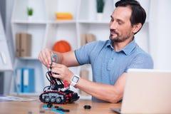 Ικανοποιημένο άτομο που συνδέει τα καλώδια με το droid στοκ εικόνα