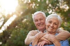 Ικανοποιημένο ανώτερο ζεύγος που χαμογελά ευτυχώς υπαίθρια από κοινού στοκ εικόνες