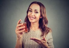 Ικανοποιημένο κορίτσι που απολαμβάνει τη μυρωδιά αρώματος στοκ φωτογραφία