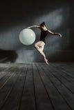 Ικανός gymnast που τεντώνει χρησιμοποιώντας το άσπρο μπαλόνι στοκ εικόνα με δικαίωμα ελεύθερης χρήσης