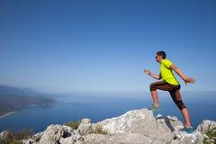 Ικανότητα, αθλητισμός, άνθρωποι και έννοια τρόπου ζωής - νεαρός άνδρας που κάνει τις ασκήσεις γιόγκας στην παραλία από την πλάτη Στοκ εικόνες με δικαίωμα ελεύθερης χρήσης