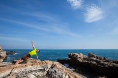 Ικανότητα, αθλητισμός, άνθρωποι και έννοια τρόπου ζωής - νεαρός άνδρας που κάνει τις ασκήσεις γιόγκας στην παραλία από την πλάτη Στοκ Εικόνες