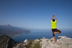 Ικανότητα, αθλητισμός, άνθρωποι και έννοια τρόπου ζωής - νεαρός άνδρας που κάνει τις ασκήσεις γιόγκας στην παραλία από την πλάτη Στοκ εικόνα με δικαίωμα ελεύθερης χρήσης