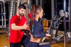 Ικανότητα, αθλητισμός, κατάρτιση και έννοια ανθρώπων - προσωπικός εκπαιδευτής που βοηθά την εργασία γυναικών με στη γυμναστική Στοκ Φωτογραφία