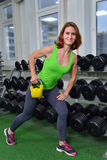 Ικανότητα, αθλητισμός, που ασκεί τον τρόπο ζωής - γυναίκα Μεσαίωνα που κάνει τις ασκήσεις με τον αλτήρα στη γυμναστική στον ευρύτ Στοκ Φωτογραφίες