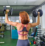 Ικανότητα, αθλητισμός, που ασκεί τον τρόπο ζωής - γυναίκα με τους αλτήρες που κάνουν τις ασκήσεις στη γυμναστική στοκ εικόνες