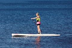 Ικανότητα ΓΟΥΛΙΑΣ - γυναίκα στον πίνακα κουπιών στη λίμνη στοκ εικόνα