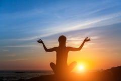Ικανότητα και υγιής τρόπος ζωής Γυναίκα περισυλλογής στον ωκεανό κατά τη διάρκεια του καταπληκτικού ηλιοβασιλέματος Στοκ Εικόνες