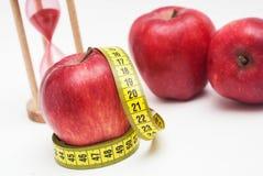 Ικανότητα και υγιή τρόφιμα Κλείστε επάνω την κόκκινη Apple με τη μέτρηση Metter και του ρολογιού γυαλιού άμμου στο υπόβαθρο Απομο Στοκ Εικόνες