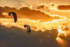 Ικτίνοι που πετούν στον αέρα στο φυσικό υπόβαθρο ουρανού ηλιοβασιλέματος Το Kitesurfing είναι δημοφιλής δραστηριότητα θερινών υπα στοκ εικόνες