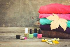 Ιματισμός και καλλυντικά γυναικών ` s: πουλόβερ, κραγιόν, στιλβωτική ουσία καρφιών, περιδέραια, κίτρινα φύλλα Στοκ Εικόνες