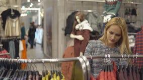 Ιματισμός, ντουλάπα, μόδα, ύφος και έννοια ανθρώπων - ευτυχής ξανθή γυναίκα που επιλέγει τον ιματισμό στο κατάστημα απόθεμα βίντεο