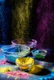 Ινδικά χρώματα φεστιβάλ Holi Διάφορα κύπελλα με τη σκόνη χρωμάτων Holi Έκρηξη του πορφυρού, κίτρινου και μπλε χρώματος στοκ φωτογραφία