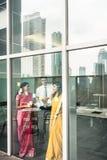 Ινδικοί υπάλληλοι που κολλούν τις υπενθυμίσεις στον τοίχο γυαλιού στο γραφείο Στοκ Εικόνες