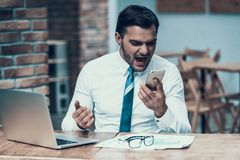 0 ινδικός επιχειρηματίας που κραυγάζει στο τηλέφωνο στην αρχή Στοκ Φωτογραφία