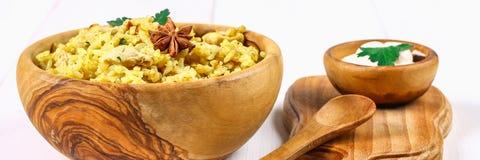 Ινδικό biryani με το κοτόπουλο, το γιαούρτι και τα καρυκεύματα σε ένα πιάτο σε έναν ξύλινο πίνακα Νέο έτος \ «s, πιάτο Χριστουγέν Στοκ Εικόνες