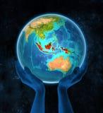 Ινδονησία στη γη στα χέρια στοκ εικόνες