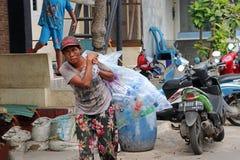 Ινδονησιακή γυναίκα που περπατά και που φέρνει τη μεγάλη πλαστική τσάντα που μέσα είναι πλήρης του πλαστικού μπουκαλιού στο δρόμο στοκ φωτογραφίες