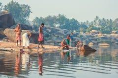 Ινδία, Hampi - 22 Δεκεμβρίου 2015: Τα άτομα πλένουν και πλένουν στην όχθη ποταμού το πρωί Στοκ Φωτογραφίες