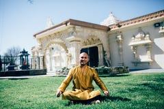 Ινδικά συνεδρίαση και χαμόγελο ατόμων Handsom σε ένα χρυσό Kurta στο ναό Στοκ Φωτογραφία