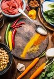 Ινδικά χορτοφάγα μαγειρεύοντας συστατικά με τα ζωηρόχρωμα επίγεια καρυκεύματα, ινδική κόλλα κάρρυ, μπιζέλια νεοσσών, λαχανικά και Στοκ φωτογραφία με δικαίωμα ελεύθερης χρήσης