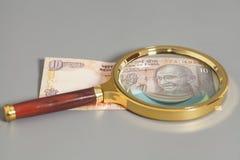 Ινδικές σημειώσεις ρουπίων νομίσματος με την ενίσχυση - γυαλί Στοκ φωτογραφία με δικαίωμα ελεύθερης χρήσης
