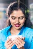 Ινδική γυναίκα με την κούπα καφέ στοκ φωτογραφία