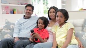 Ινδική οικογενειακή συνεδρίαση στον καναπέ που προσέχει τη TV από κοινού φιλμ μικρού μήκους