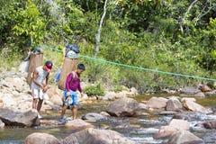Ινδικοί εγγενείς οδηγοί που διασχίζουν τον ποταμό με τα παραδοσιακά σακίδια πλάτης Στοκ φωτογραφία με δικαίωμα ελεύθερης χρήσης