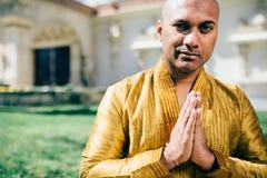 Ινδικός χαιρετισμός Namaste ατόμων Handsom σε χρυσό Kurta στο ναό Στοκ Εικόνα