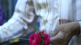 Ινδικό άτομο που συσσωρεύει επάνω τα ζωηρόχρωμα λουλούδια σε μια μεγάλη βελόνα απόθεμα βίντεο