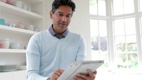 Ινδικό άτομο που χρησιμοποιεί την ψηφιακή ταμπλέτα στην κουζίνα στο σπίτι απόθεμα βίντεο