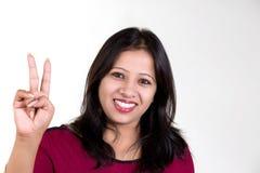 Ινδικό κορίτσι που φορά την κόκκινη μπλούζα που παρουσιάζει νίκη που πυροβολείται ενάντια στο wh Στοκ φωτογραφία με δικαίωμα ελεύθερης χρήσης