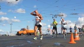 30 Ιουνίου 2019 η Αγία Πετρούπολη: Οι δρομείς μαραθωνίου τρέχουν την απόσταση και πίνουν το νερό μετά από το στοιχείο με το νερό, φιλμ μικρού μήκους